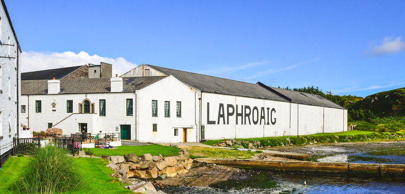 The Laphroaig distiller in Scotland. Green grass and old buildings next to a stream